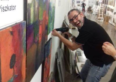 Zoli is getting the paintings up on Ildiko's wall