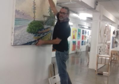 Zoli is putting the paintings up